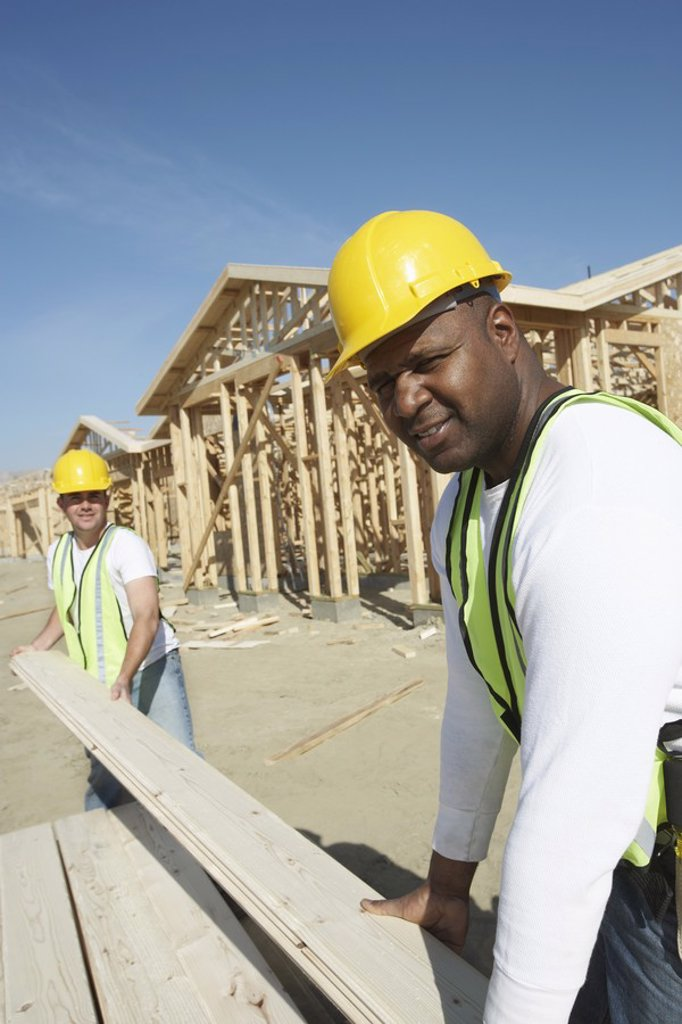 Construction Workers Stacking Timber : Stock Photo