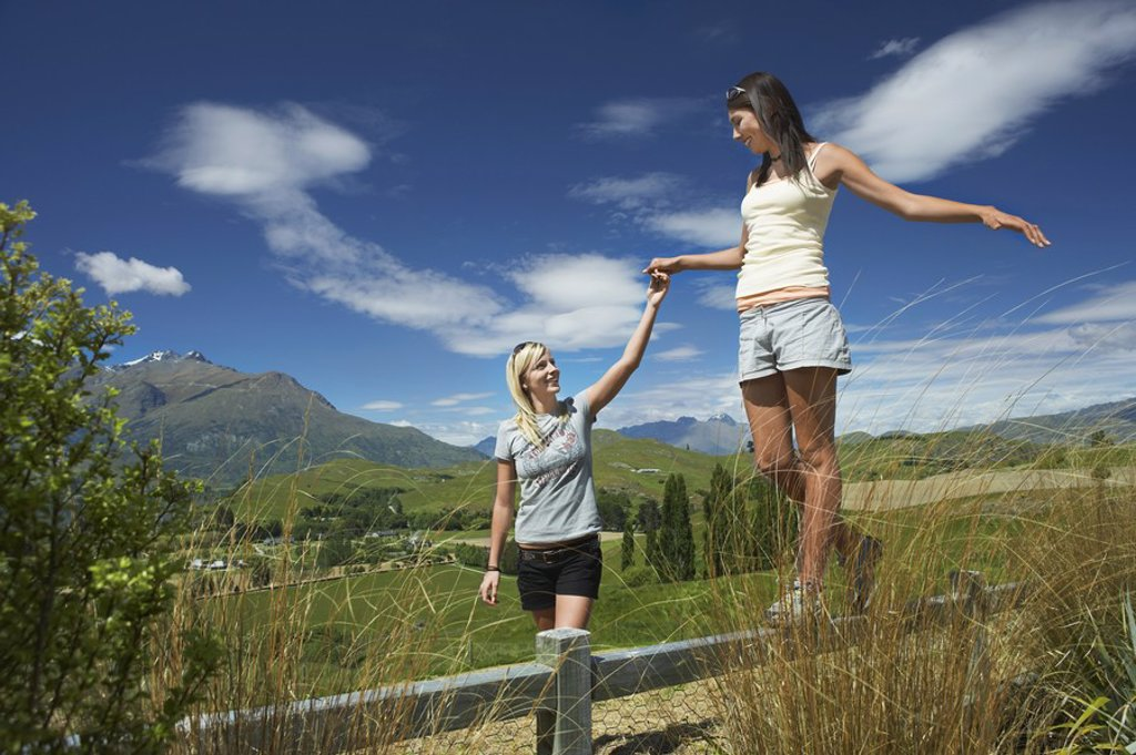 Woman helping another woman walk along fence in countryside : Stock Photo