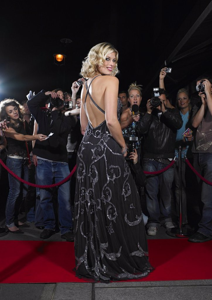 Stock Photo: 1654R-16879 Woman posing on red carpet in front of fans