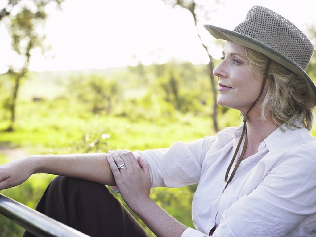 Portrait of adult woman sitting wearing hat thinking : Stock Photo