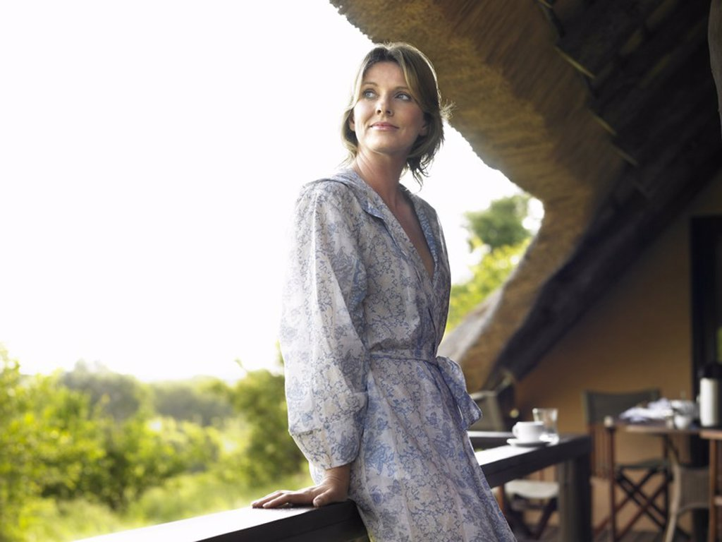 Stock Photo: 1654R-17022 Portrait of adult woman on terrace in bathrobe looking over shoulder