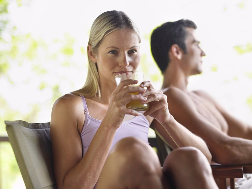Couple sitting outdoors woman drinking juice focus on foreground : Stock Photo