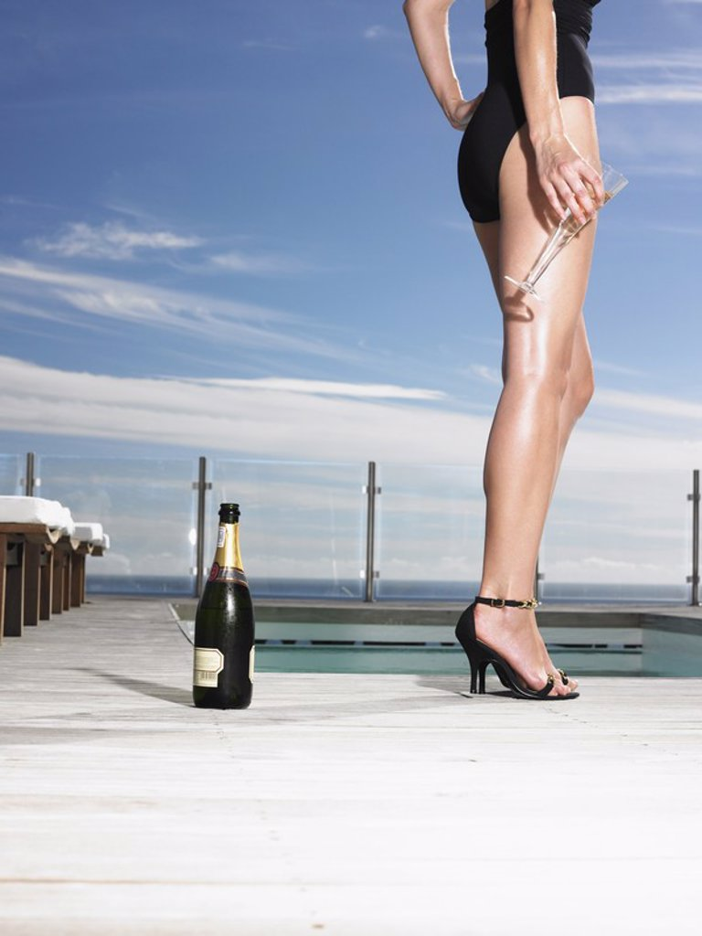 Woman in bathing suit standing with champagne at outdoor pool low section : Stock Photo