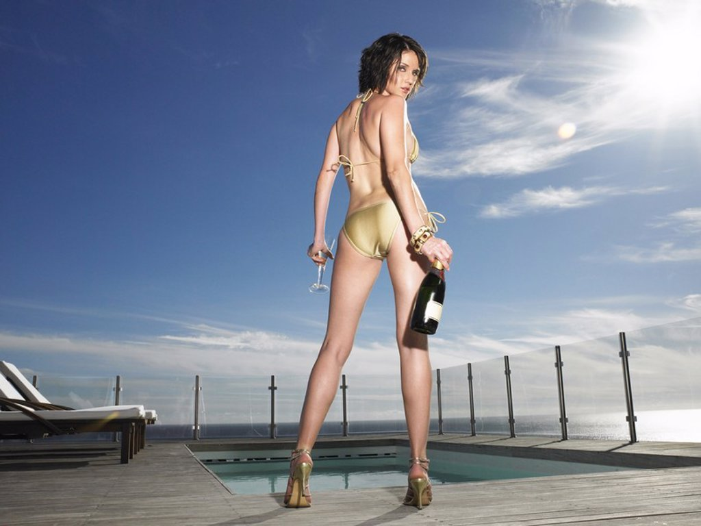 Woman in bathing suit standing with champagne at outdoor pool back view : Stock Photo