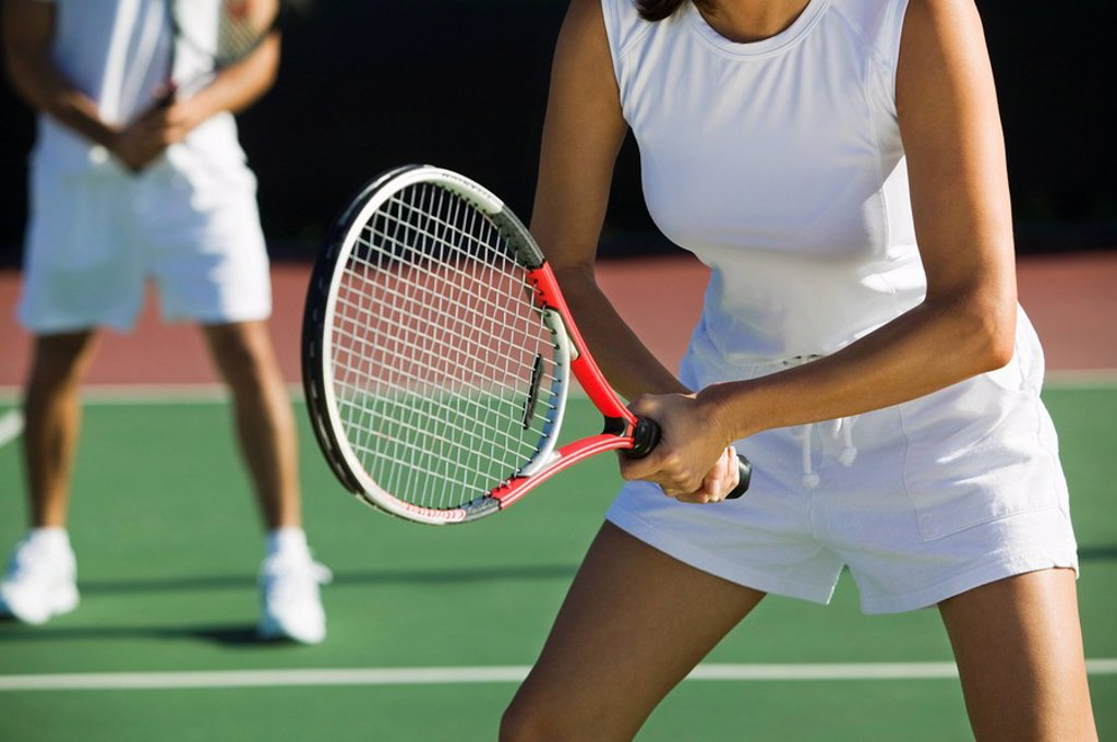 Stock Photo: 1654R-1708 Mixed doubles tennis players on court focus on woman mid section