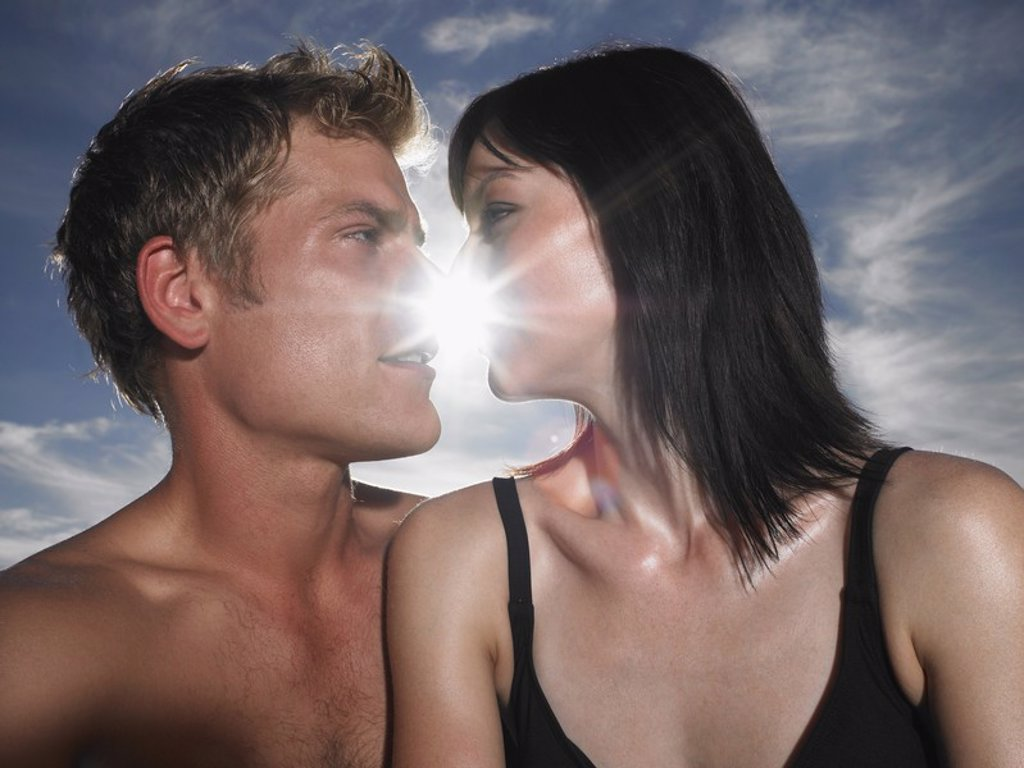 Couple about to kiss with sun behind outdoors : Stock Photo
