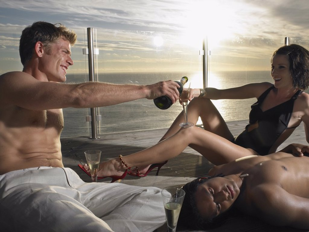 Young people pouring champagne on deck at sunset near ocean : Stock Photo