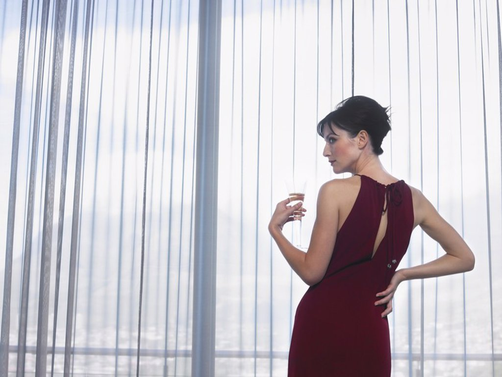 Woman wearing elegant dress looking out of window indoors : Stock Photo