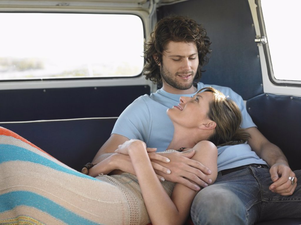 Affectionate Young Couple Relaxing in Camper Van : Stock Photo