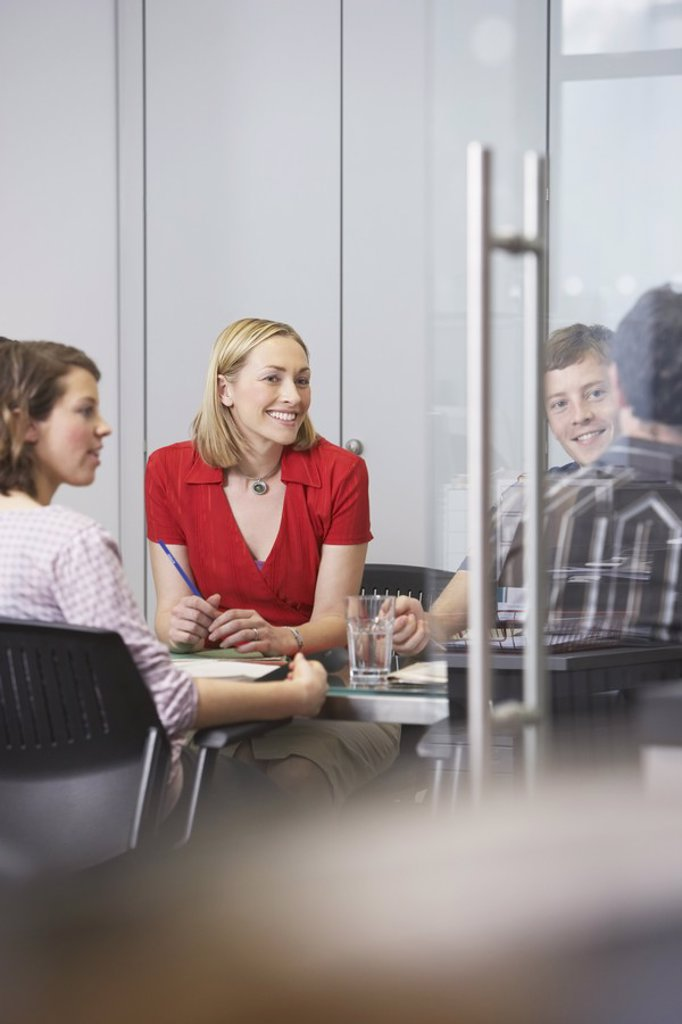 Office workers sitting around conference table : Stock Photo
