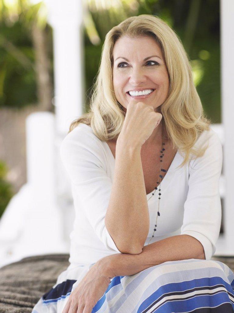 Woman sitting on verandah portrait : Stock Photo