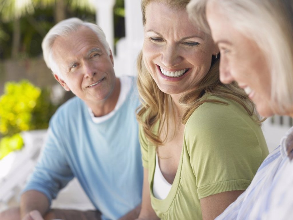 Stock Photo: 1654R-17376 Three people sitting on verandah