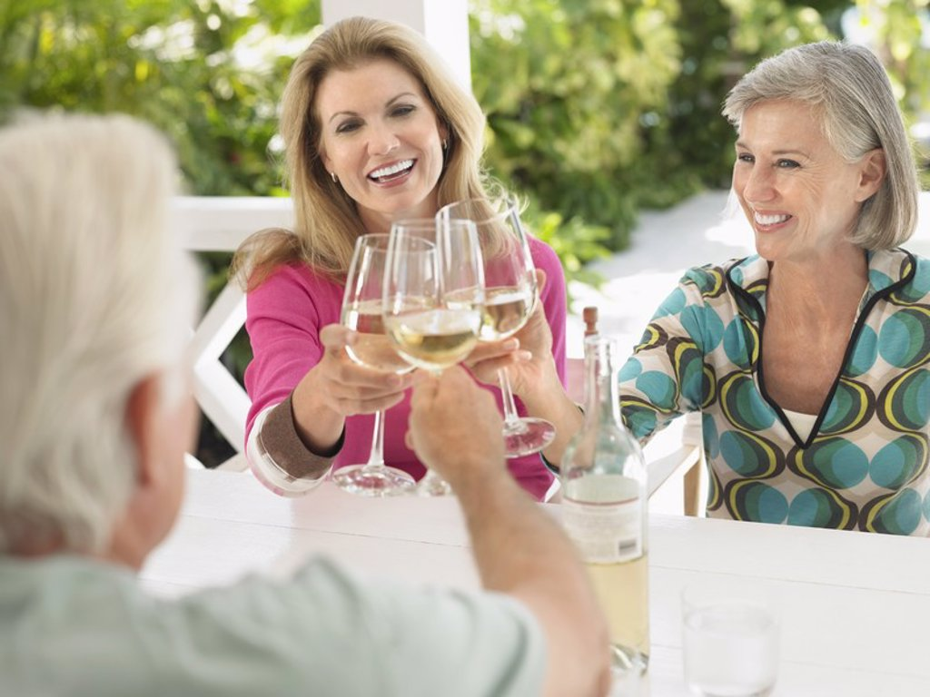 Three people toasting with wine glasses sitting at verandah table : Stock Photo