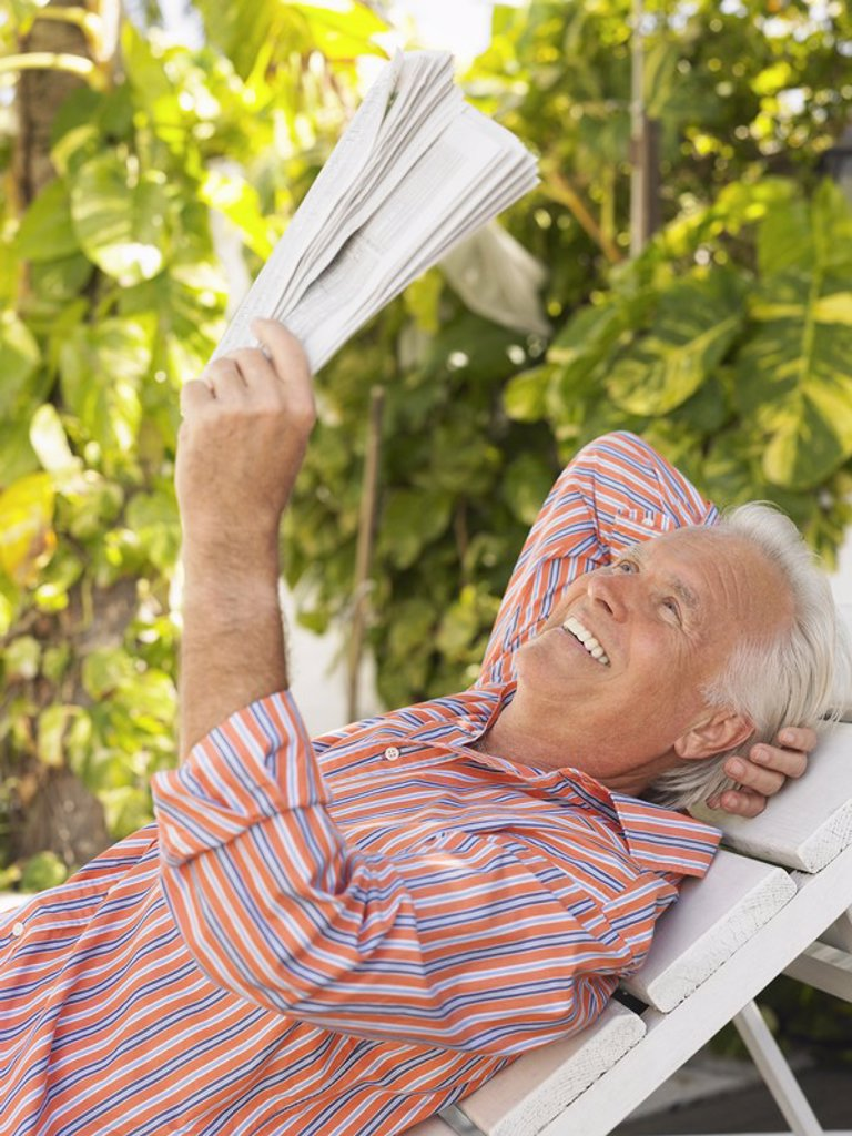 Stock Photo: 1654R-17395 Man reclining on lounge chair reading newspaper side view