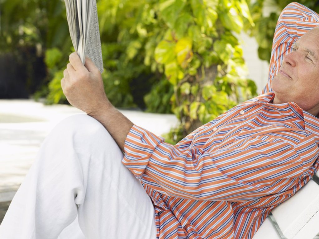 Stock Photo: 1654R-17396 Man reclining on lounge chair reading newspaper side view