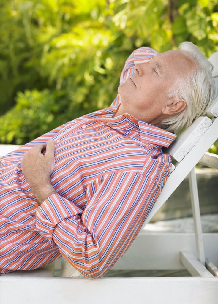 Man reclining on lounge chair outdoors side view : Stock Photo