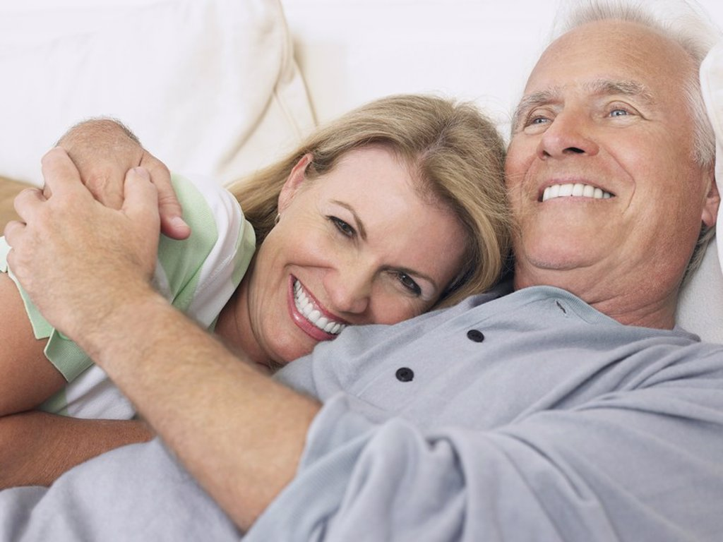 Couple embracing lying in bed : Stock Photo