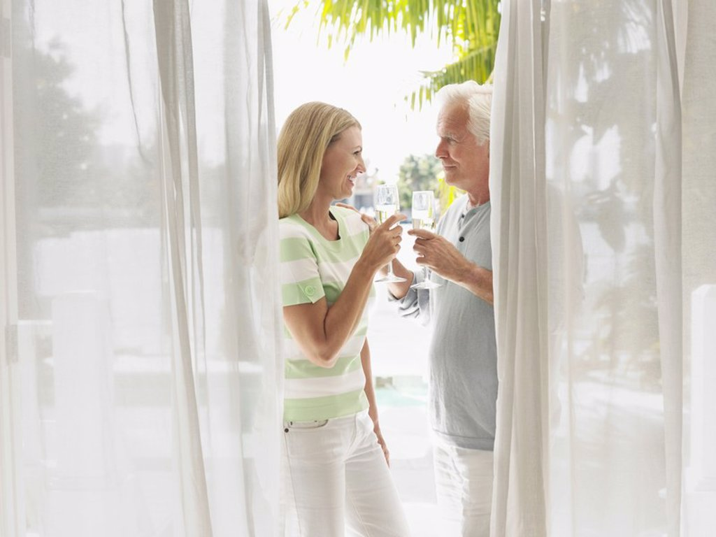 Couple toasting with champagne flutes standing on verandah side view : Stock Photo