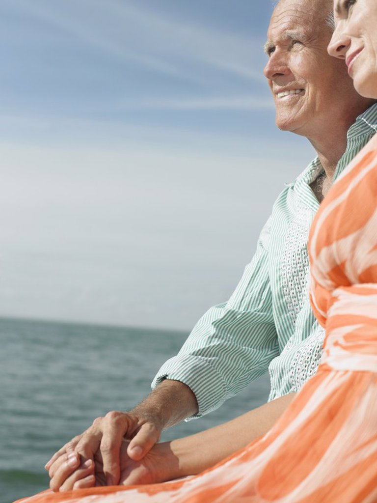 Couple sitting on edge of pier looking at view side view : Stock Photo