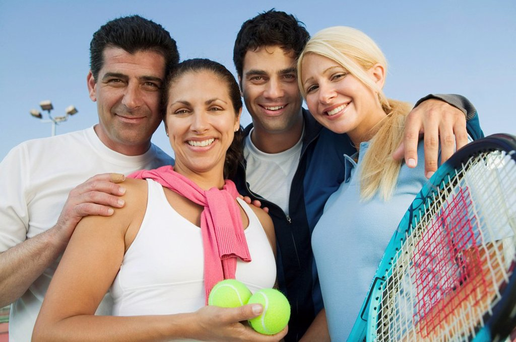 Stock Photo: 1654R-1747 Four mixed doubles tennis players by net at tennis court portrait
