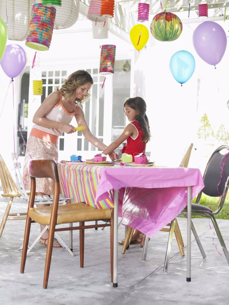 Stock Photo: 1654R-17504 Mother and daughter 7_9 laying table for birthday party side view