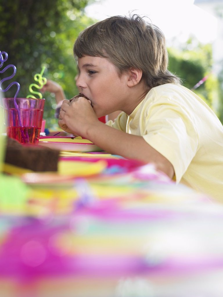 Young boy 10_12 eating cupcake at birthday party : Stock Photo