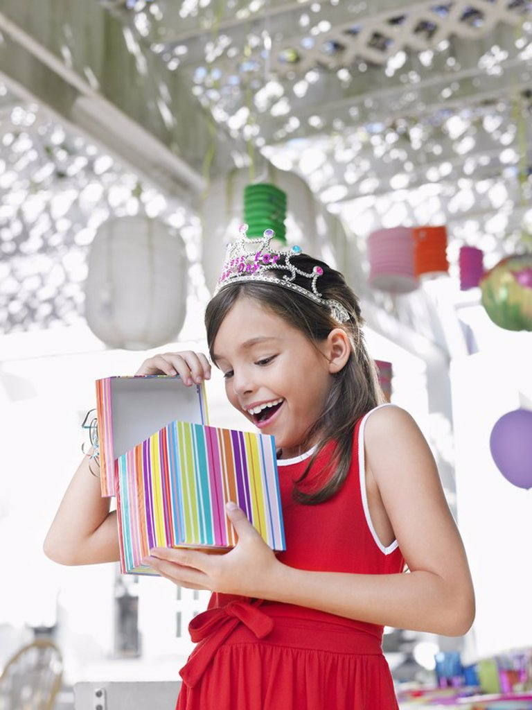 Young girl 7_9 opening birthday present at party : Stock Photo