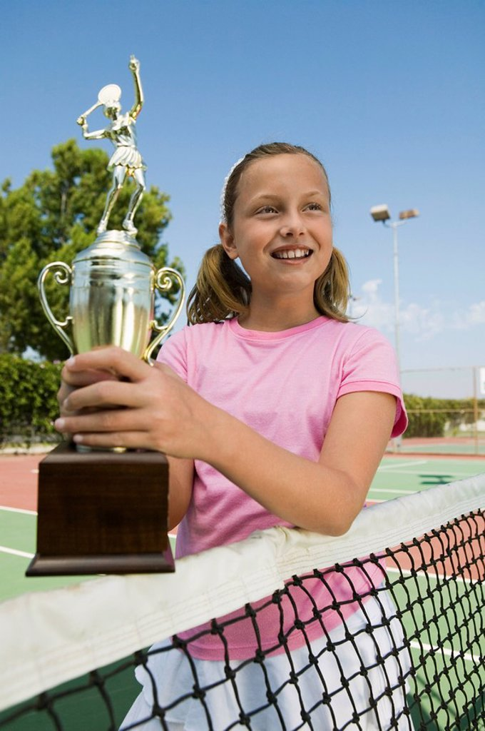 Girl at Tennis Net Holding Trophy : Stock Photo