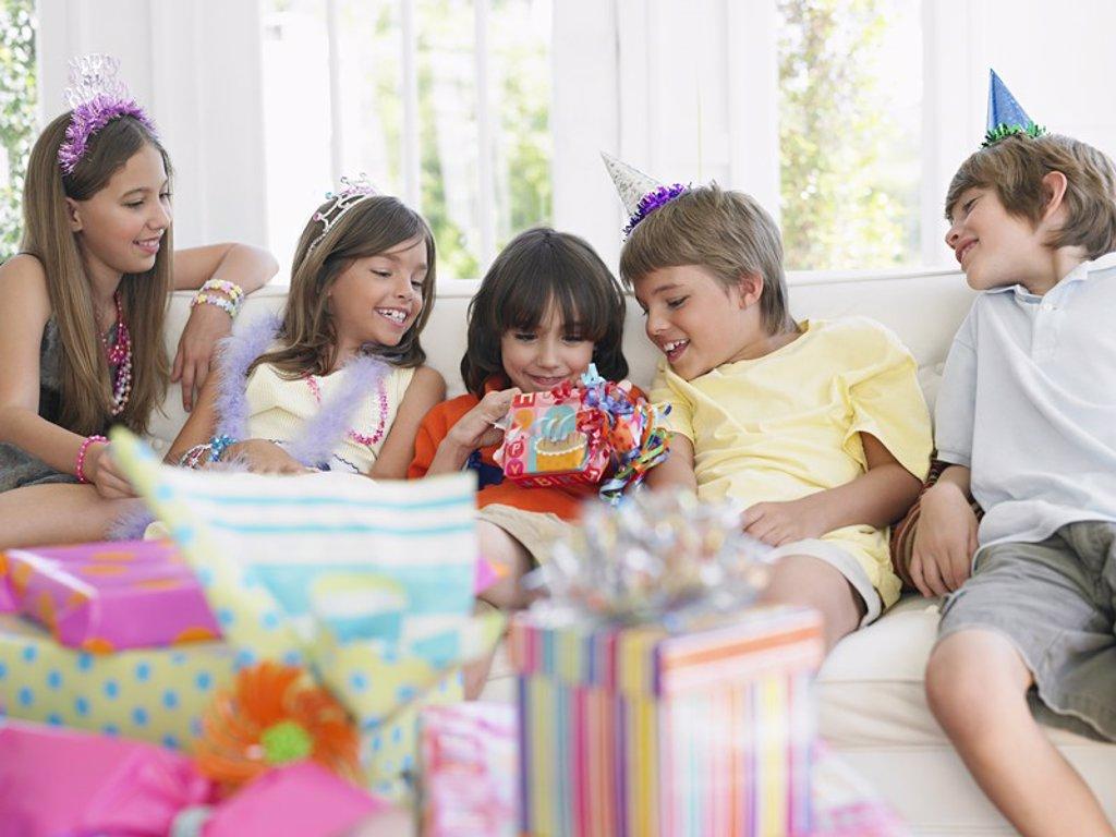 Children 7_12 sitting on sofa watching one open birthday present : Stock Photo
