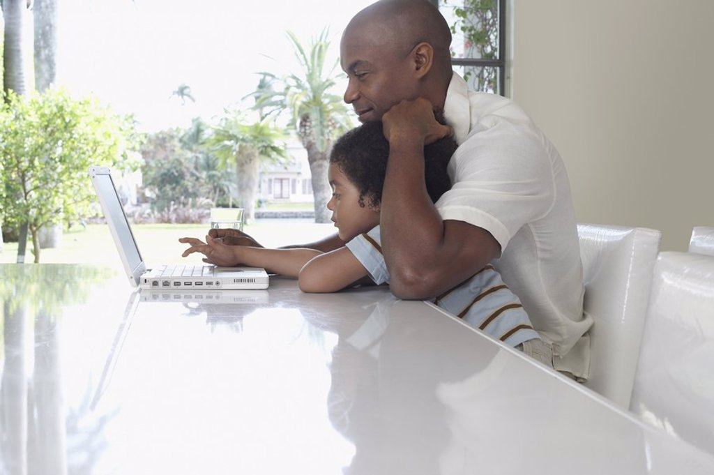 Father and son 5_6 years using laptop in dining room side view : Stock Photo