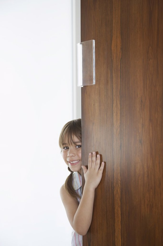 Girl 5_6 peeking from behind door : Stock Photo