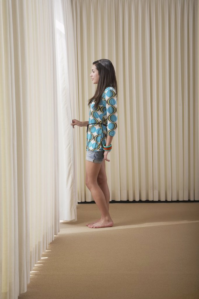 Teenage girl 16_18 standing in empty room drawing aside blinds side view : Stock Photo