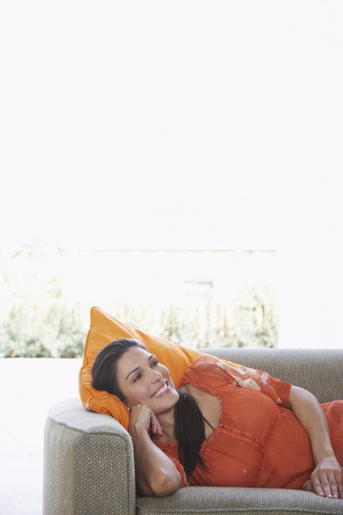 Mid_adult woman lying on sofa smiling : Stock Photo