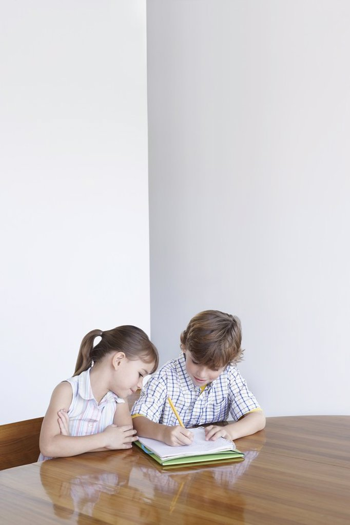 Boy 7_9 and girl 5_6 doing homework together : Stock Photo