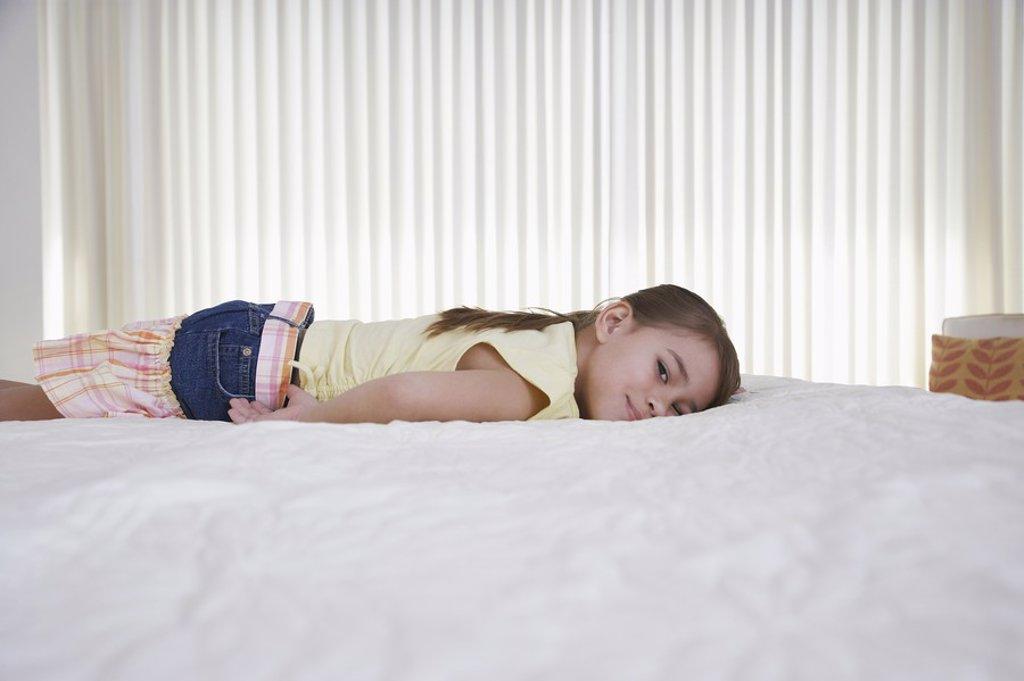 Girl 5_6 lying on bed : Stock Photo