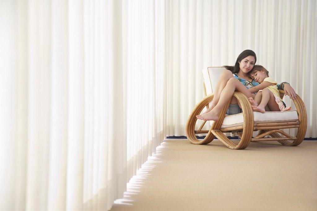 Teenage girl 16_18 sitting on armchair with sister 5_6 : Stock Photo