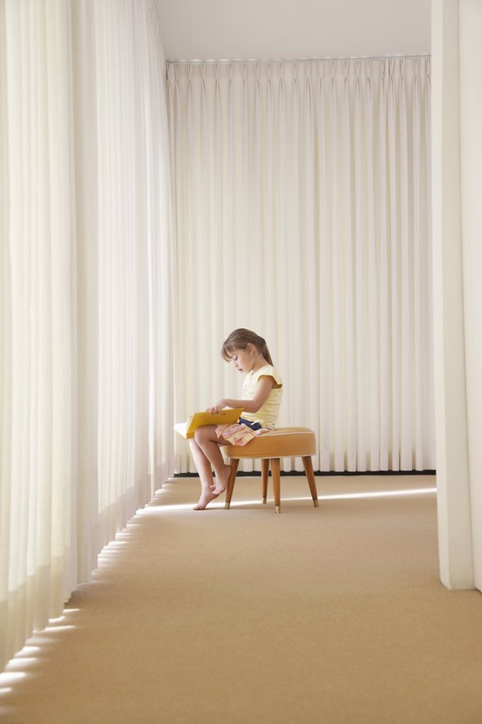 Stock Photo: 1654R-17728 Girl 5_6 sitting on stool in room reading book side view