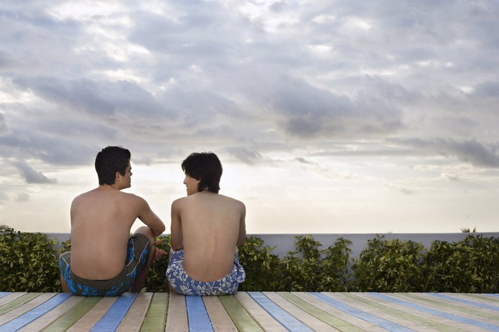 Two teenage boys 16_17 sitting on wooden deck back view : Stock Photo