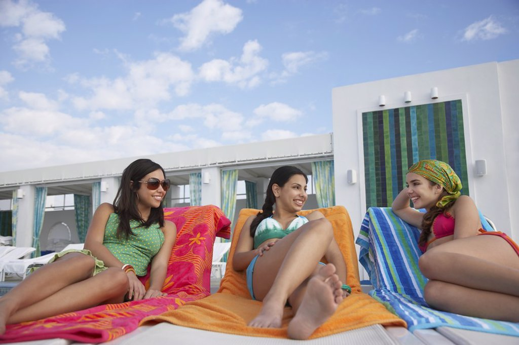 Three teenage girls 16_17 lying on sunloungers : Stock Photo