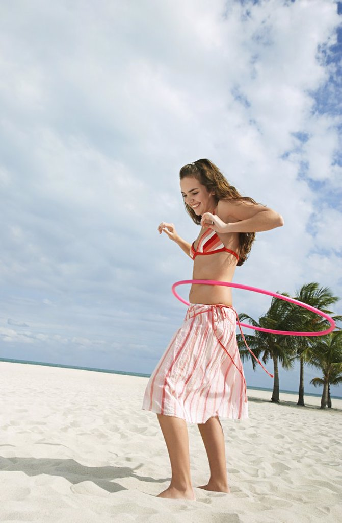 Teenage girl 16_17 playing with hoola hoop on beach : Stock Photo