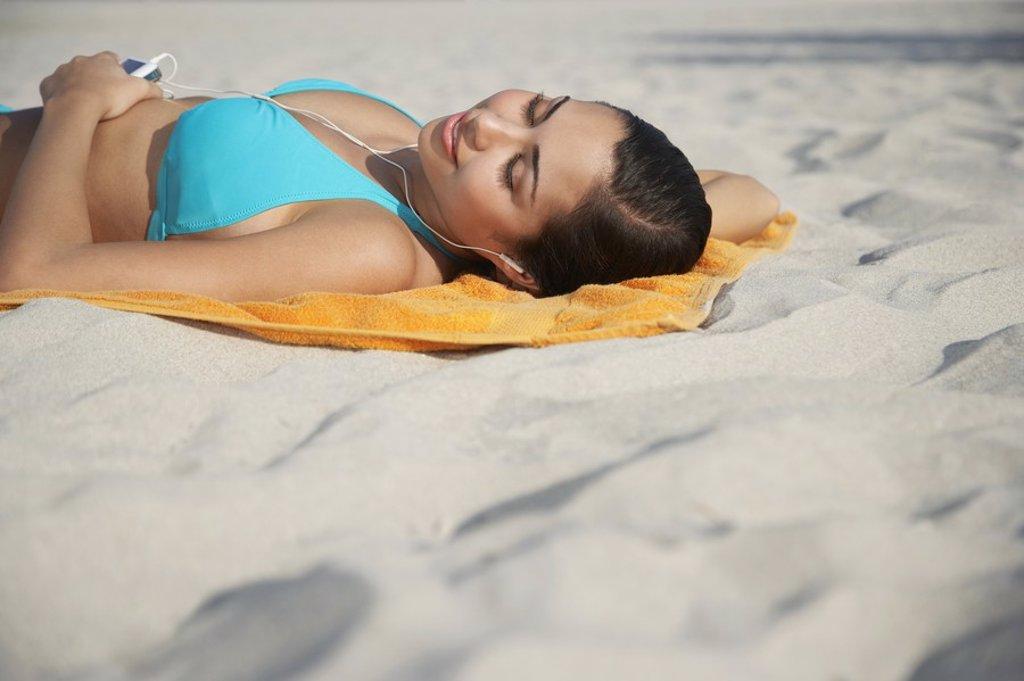 Teenage girl 16_17 using mp3 player lying on beach : Stock Photo