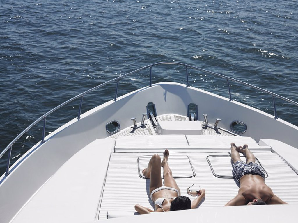Young couple sunbathing on bow of yacht at sea elevated view : Stock Photo