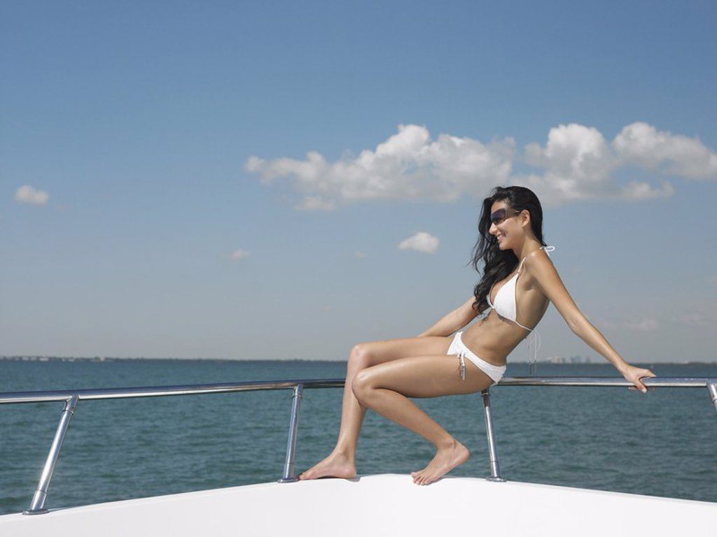 Young woman in bikini sitting on bow of yacht side view : Stock Photo