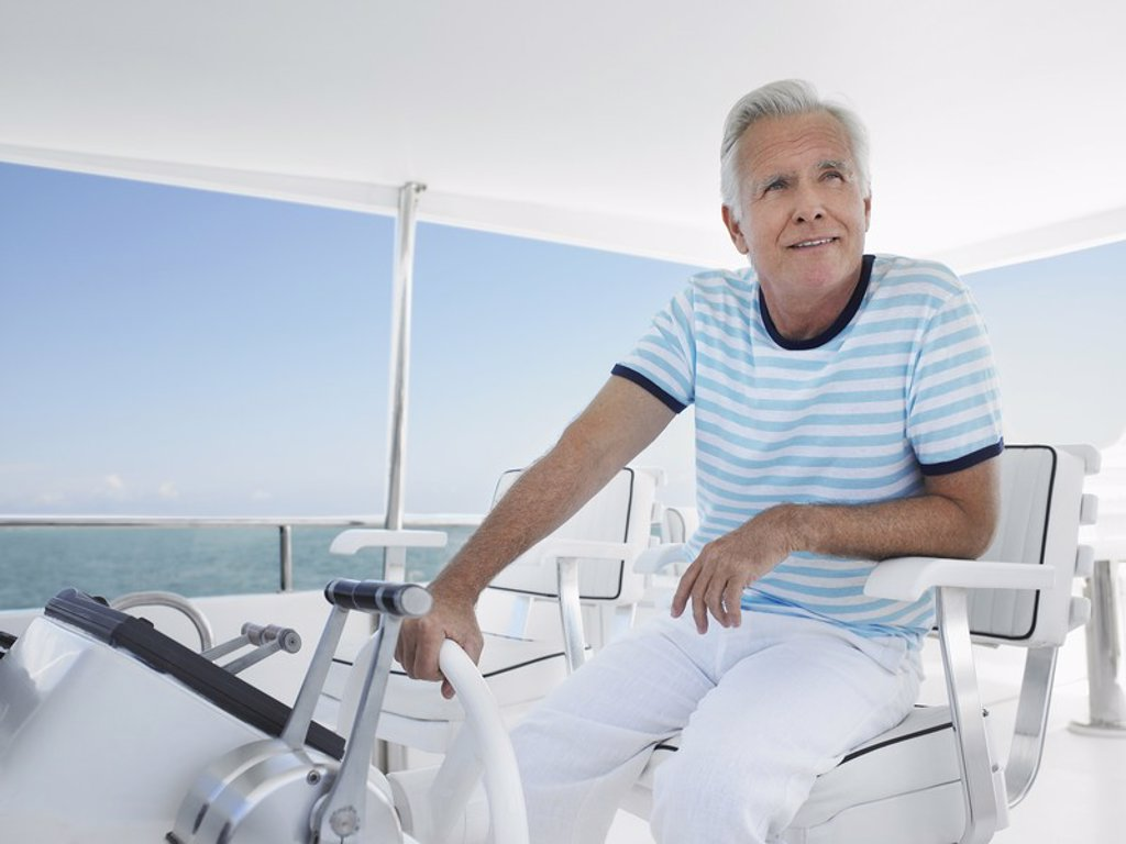 Middle_aged man sitting at helm of yacht : Stock Photo