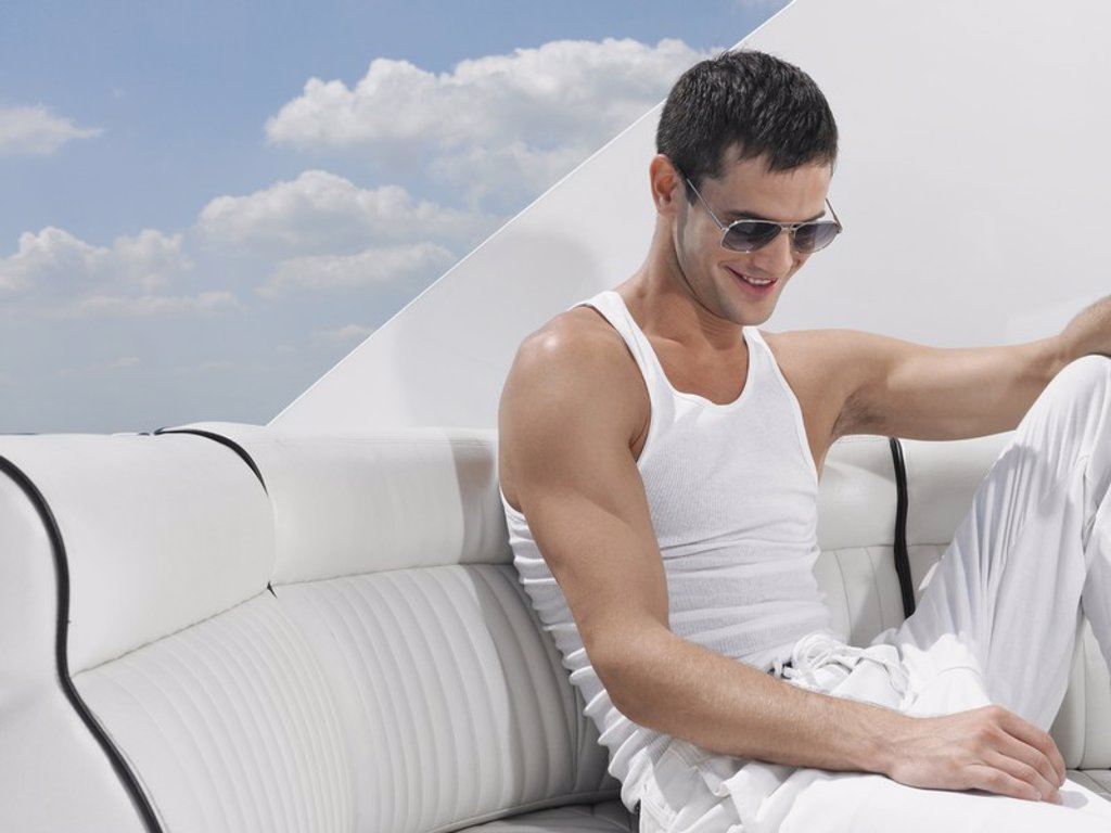 Young man relaxing on yacht : Stock Photo