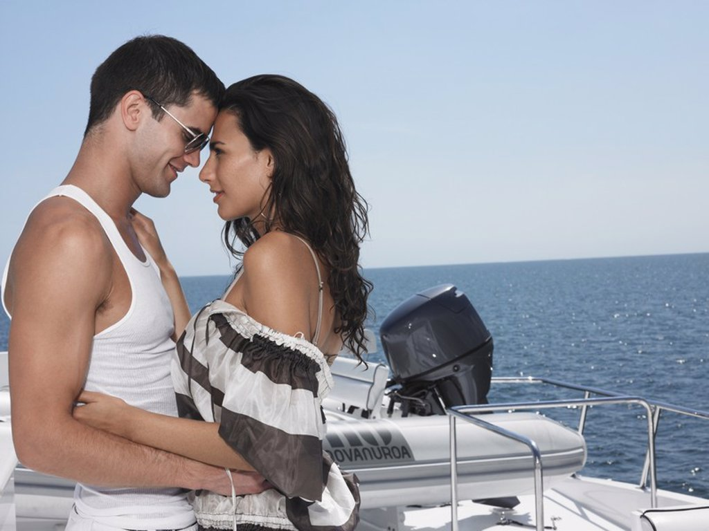 Stock Photo: 1654R-17845 Young couple embracing on yacht profile
