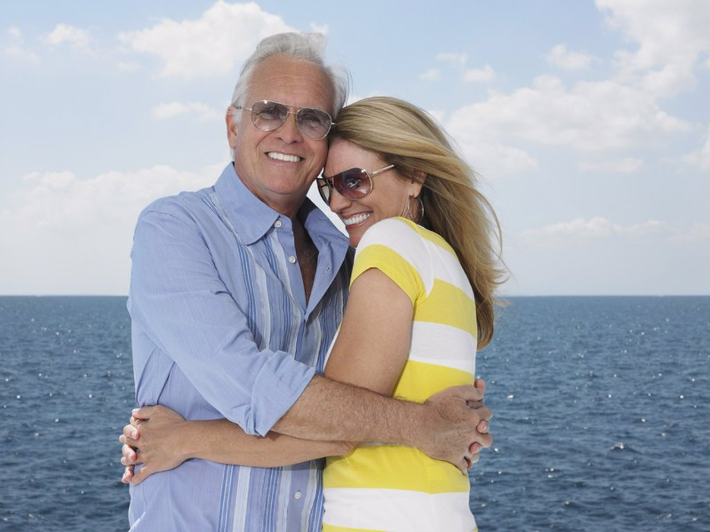 Stock Photo: 1654R-17848 Middle_aged couple embracing against sea portrait