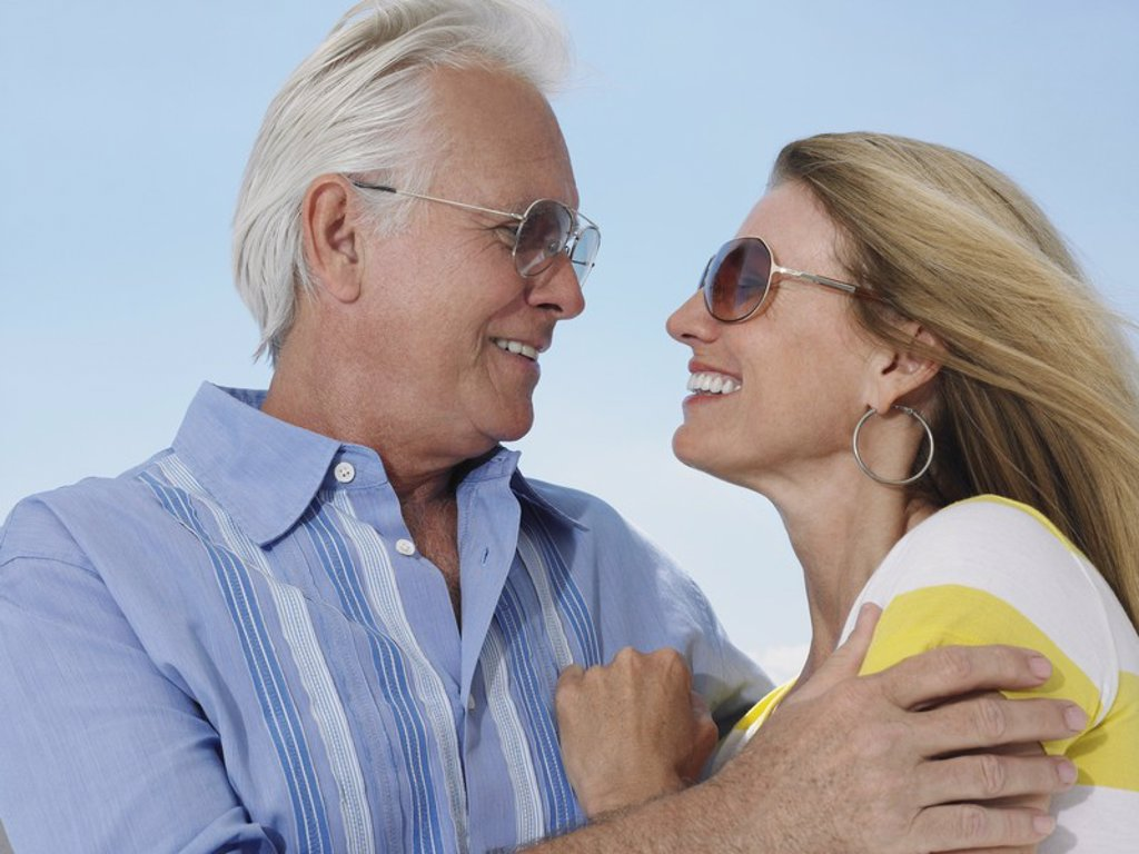 Middle_aged couple embracing and looking in eyes against sky : Stock Photo