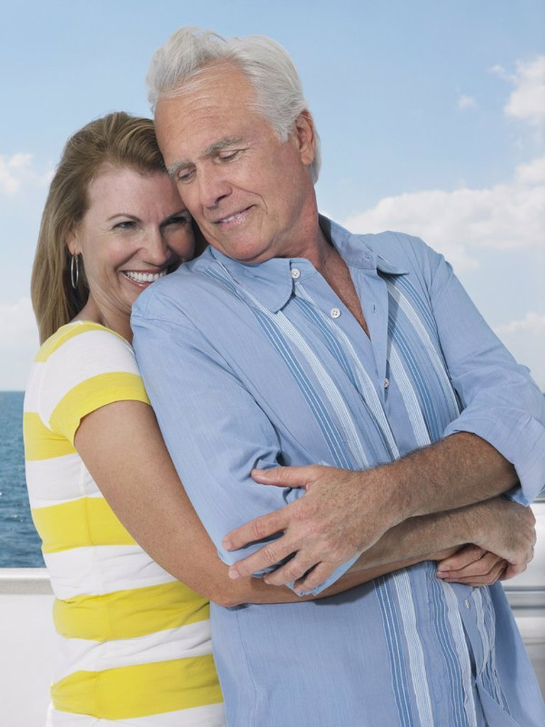 Stock Photo: 1654R-17851 Middle_aged couple embracing on yacht
