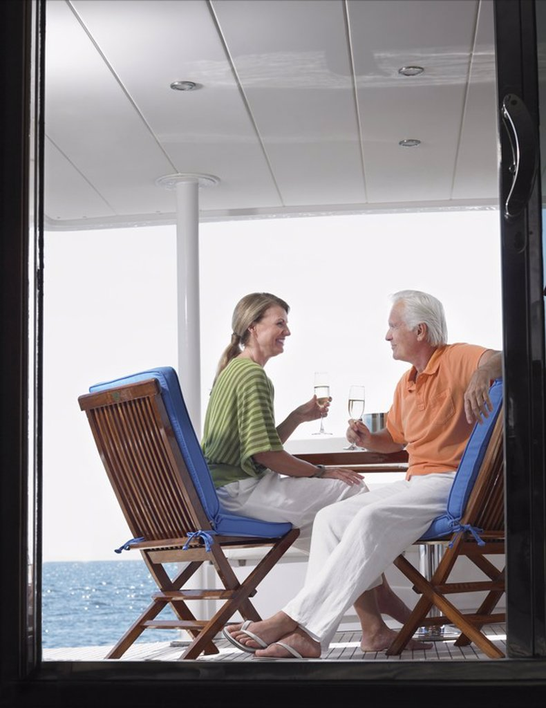Stock Photo: 1654R-17852 Middle_aged couple drinking wine on yacht profile view through door